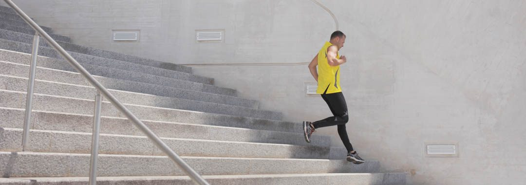 Man in yellow t-shirt running on concrete steps