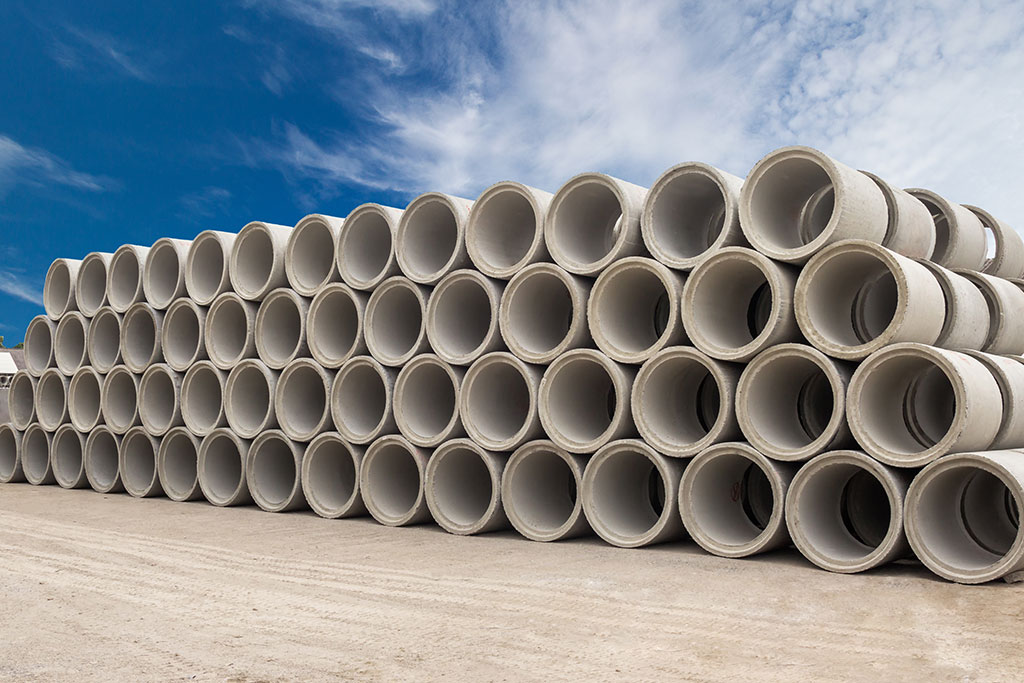 Concrete piping stacked up under a blue sky