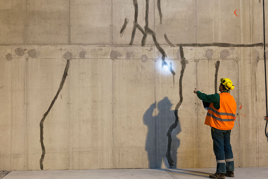 A concrete wall being inspected by a worker